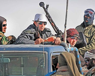 Libyan rebels who are part of the forces against Libyan leader Moammar Gadhafi ride on an armed truck near Ras Lanuf, eastern Libya, Monday, March 7, 2011.