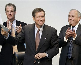 Ohio Governor John Kasich holds up paperwork signifying that American Greetings Corp., with 2,000 employees, will remain in northeast Ohio, at the company's headquarters in Brooklyn, Ohio on Monday, March 7, 2011. With Kasich are Mark Kvamme, Ohio's Development Director, left, and Morry Weiss, Chairman of American Greetings.