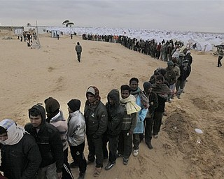 Men from Bangladesh, who used to work in Libya and fled the unrest in the country, wait in line for food in a refugee camp at  the Tunisia-Libyan border, in Ras Ajdir, Tunisia, Tuesday March 8, 2011. The 20,000-capacity transit camp for thousands of migrant workers who have fled the fighting in Libya in the past two weeks is about seven kilometers (four miles) from the Libyan border and is expanding with each day of crisis in Libya.