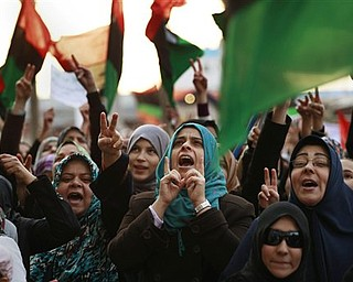 Libyan women, some holding pre-Gadhafi flags chant during a protest to demand the resignation of Libyan leader Moammar Gadhafi and the implementation of a no-fly zone, in Benghazi, eastern Libya, Thursday, March 10, 2011.