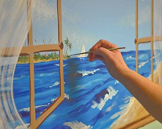 With her paint pallet at hand, Linda Clark selects the right color or mixes colors to achieve the effect she wants to create in a beach scene mural.