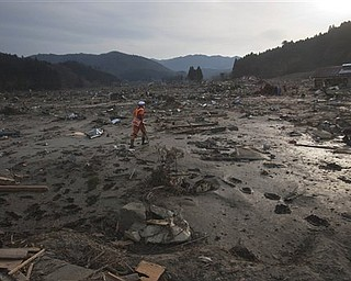 A Japanese rescue team member walks through the completely leveled village of Saito in northeastern Japan Monday, March 14, 2011. Rescue workers used chain saws and hand picks Monday to dig out bodies in Japan's devastated coastal towns, as Asia's richest nation faced a mounting humanitarian, nuclear and economic crisis in the aftermath of a massive earthquake and tsunami that likely killed thousands.