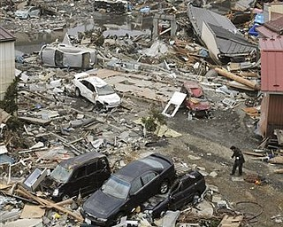 People carry the body of a victim through debris in Kesennuma, Miyagi, northern Japan Tuesday, March 15, 2011 following Friday's massive earthquake and the ensuing tsunami.