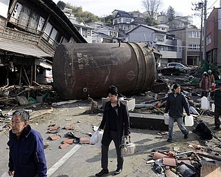 People walk to receive water supply through a street with the rubble Monday March 14, 2011 in Kesennuma, Miyagi Prefecture, northern Japan following Friday's massive earthquake and the ensuing tsunami.