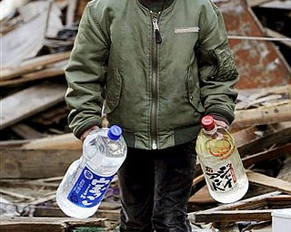 Boy carries bottles of water amid debris in Kesennuma, northern Japan Monday, March 14, 2011 following Friday's massive earthquake and the ensuing tsunami.
