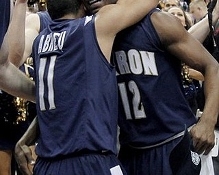 Akron's Darryl Roberts (12) and Alex Abreu (11) hug after Akron won the NCAA college basketball Mid-American Conference championship 66-65 over Kent State in overtime Saturday, March 12, 2011, in Cleveland.