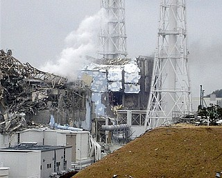 This image made available from Tokyo Electric Power Co. via Kyodo News, shows the damaged No. 4 unit of the Fukushima Dai-ichi nuclear complex in Okumamachi, northeastern Japan, on Tuesday March 15, 2011. White smoke billows from the No. 3 unit.