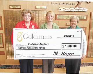 Fair exchange: The Auxiliary of St. Joseph Health Center, 667 Eastland SE, Warren, received a check for $1,800 following a recent sale of unwanted gold and silver jewelry. The items were taken to Goldman's in Boardman and exchanged for cash. At the end of the sale Goldman's presented a check for a percentage of the sales to the auxiliary. Displaying a big symbolic check are, from left, Alice Flask, auxiliary project chairwoman; Laura Hanna, a representative of Goldman's; and Fran Cunningham, auxiliary president.