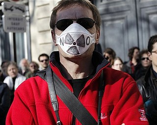A demonstrator wears gas mask during an anti-nuclear protest in Paris, Sunday, March 20, 2011. Fueled by the nuclear crisis unfolding in Japan following the country's earthquake, demonstrators are demanding that France end its dependence on nuclear power.