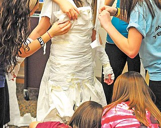 Jena Yambrovich gets a toilet paper wedding dress from her fellow South Range High School classmates at a Sisterhood Project event. The Sisterhood Project acts as a support group for freshman girls by integrating them with members of the senior class.