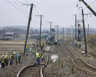 Workers repair the railway tracks damaged by the March 11 earthquake in Hitachinaka, Ibaraki Prefecture, Japan, Monday, March 21, 2011.