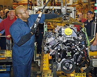 In this file photo taken Dec. 18, 2009, Willie Ray, an employee of GM, hoists the last big block V8 engine from the assembly line at the General Motors Powertrain plant in Tonawanda, N.Y. General Motors Co. is halting some production at its Buffalo, N.Y., engine plant because of a slowdown in parts from Japan.