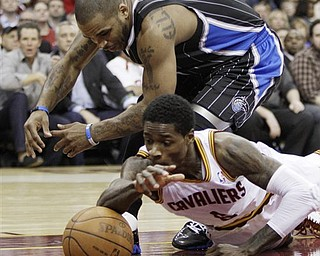 Orlando Magic's Jameer Nelson, top, and Cleveland Cavaliers' Manny Harris battle for a loose ball in the second quarter in an NBA basketball game, Monday, March 21, 2011, in Cleveland.