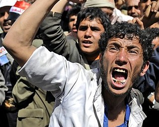 An anti-government protestor shouts slogans during a demonstration demanding the resignation of Yemeni President Ali Abdullah Saleh,  in Sanaa,Yemen, Monday, March 21, 2011. Three Yemeni army commanders, including a top general, defected Monday to the opposition calling for an end to President Ali Abdullah Saleh's rule, as army tanks and armored vehicles deployed in support of thousands protesting in the capital. With the defection, it appeared Saleh's support was eroding from every power base in the nation - his own tribe called on him to step down, he fired his entire Cabinet ahead of what one government official said was a planned mass resignation, and his ambassador to the U.N. and human rights minister quit.
