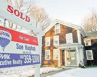 In this file photo taken Jan. 10, 2011, a sold sign is seen in front of a home, in Millis, Mass. New home? Or existing one? For buyers, the decision is getting easier. A wave of foreclosures has sent prices of previously occupied homes sinking. New-home prices have fallen much less.