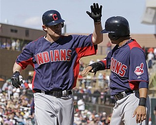 Cleveland Indians' Austin Kearns, left, is greeted by teammate Shin-Soo Choo, right, after hitting a two-run home run of Arizona Diamondbacks relief pitcher Carlos Rosa during the sixth inning of their spring training baseball game at Salt River Fields at Talking Stick near Scottsdale, Ariz., Tuesday, March 22, 2011.