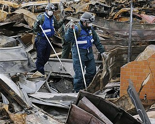 Japan Air Self-Defense Force's members search for missing persons through debris in the March 11 earthquake and tsunami-destroyed town of Yamada, northern Japan Wednesday, March 23, 2011.