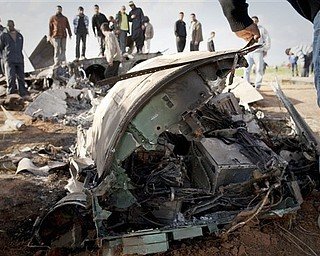 Libyans inspect the wreckage of a US  F15 fighter jet after it crashed in an open field in the village of  Bu Mariem, east of Benghazi, eastern Libya, Tuesday, March 22, 2011, with both crew ejecting safely. The U.S. Africa Command said both crew members were safe after what was believed to be a mechanical failure of the Air Force F-15. The aircraft, based out of Royal Air Force Lakenheath, England, was flying out of Italy's Aviano Air Base in support of Operation Odyssey Dawn.