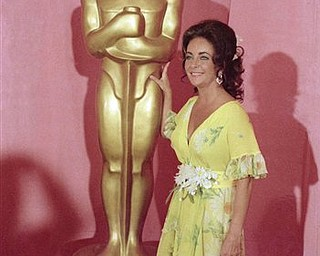 This April 2, 1974 file photo shows actress Elizabeth Taylor standing by a statue of the Academy Award Oscar in Los Angeles.  Elizabeth Taylor had it all: the violet, almond-shaped eyes, the creamy skin, the pouty lips and raven hair. Of course, there were her Oscars, iconic roles and many husbands, too, but Taylor is indeed most renowned for her beauty. She died Wednesday at age 79 of congestive heart failure.