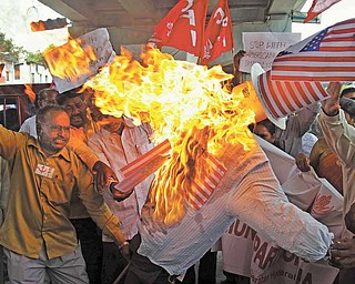 Activists of Communist Party of India burn an effigy of the United States as they protest against the military attack on Libya by the U.S., in Hyderabad, India, Friday, March 25, 2011. NATO's military staff is drawing up detailed plans to assume full control of the no-fly zone over Libya in coming days, after member nations agreed to take on the operation from a U.S.-led coalition.