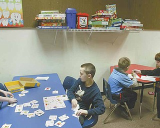 Tammy Chumley, far right, a teacher at the Rich Center for Autism at Youngstown State University, works with students at the center. The center is located on the first floor of Fedor Hall at YSU. With 70 students and 35 staff members, the center is contemplating a move to larger quarters.