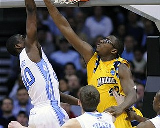 Marquette Chris Otule (42) reaches through the basket to block a shot by North Carolina's Harrison Barnes (40) during the second half of an an East regional semifinal game in the NCAA college basketball tournament Friday, March 25, 2011, in Newark, N.J.