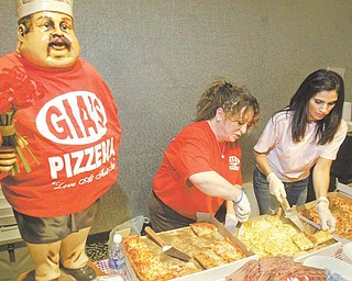 Lori Greenwalt, left, and Lynn Guerrieri of Gia's Pizzeria in Boardman serve up their specialties during The Mahoning Valley Pizza Cook-off on Sunday.