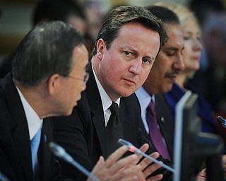 British Prime Minister David Cameron, centre,   listens to UN Secretary General Ban Ki-Moon, left,  speak at the opening of the Libya Conference in London Tuesday March 29, 2011.  International leaders plotted out an endgame Tuesday for Moammar Gadhafi's tottering regime, as British Prime Minister David Cameron accused the Libyan leader of shooting and starving his opponents into submission.