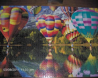"While waiting for the arrival of spring, Pete Dumas of Austintown and his wife spend many hours putting together puzzles their family gave them for Christmas. Here's a 2,000-piece puzzle they did called ""Balloons."""