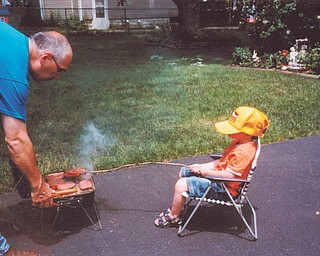 "Cooper Wilson, 5, cooks with his ""Papa,"" James Cardelein, as they get ready for a Memorial Day picnic. The photo, from 2010, was submitted by Cooper's great-grandma, Irene Cardelein of Youngstown."