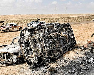 A Libyan rebel walks past the charred remains of the vehicles, belonging to the Libyan rebels, which were allegedly targeted killed in NATO coalition airstrike overnight at the front line near Brega, Libya, Saturday, April 2, 2011. NATO said on Saturday that it was investigating Libyan rebel reports that a coalition warplane had struck a rebel position that was firing into the air near the eastern front line of the battle with Gadhafi's forces.