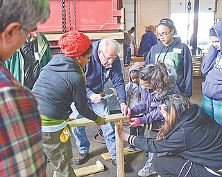 Bob McGowan of Youngstown, a member of the Men's Garden Club of Youngstown, builds a tiered strawberry planter with community gardeners from St. Patrick Church on Saturday afternoon at Emch Spring Service in Youngstown.