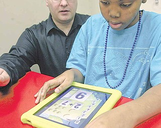Curtis Bevly, a student at the Rich Center for Autism at Youngstown State University, uses an iPad while Brendan Considine, classroom supervisor at the center, watches. The center bought the devices using a federal grant. Officials say that because of their use of visual elements and their immediacy, iPads work well for children with autism.