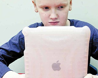 Chris Blair, a student at the Rich Center for Autism at Youngstown State University, uses an iPad. The devices help children with the disorder with language and other skills.