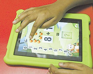 A student at the Rich Center for Autism at Youngstown State University uses an iPad application that teaches math.