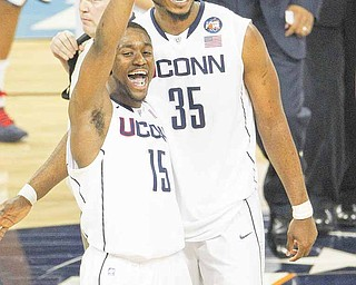 Kemba Walker, left, and Charles Okwandu of Connecticut celebrate a 56-55 victory over Kentucky in the men's NCAA Final Four semifinals at Reliant Stadium in Houston, Texas, Saturday, April 2, 2011.
