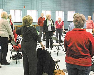 "Eve Bevilacqua, local fitness instructor, talks to those attending a ""Well of Body"" class about how stretch bands can be used to exercise in a stationary position. The program was Tuesday at the Ursuline Center in Canfield."
