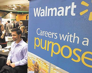 In this March 4, 2011 photo, representatives from Walmart speak to job seekers at the 32nd Annual Spring Career Fair at Cleveland State University. Over 120 organizations were on hand to talk to prospective candidates about employment and internships.