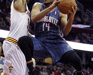 Charlotte Bobcats' D.J. Augustin (14) puts up a shot against Cleveland Cavaliers' Alonzo Gee in the first quarter during an NBA basketball game Tuesday April 5, 2011, in Cleveland.
