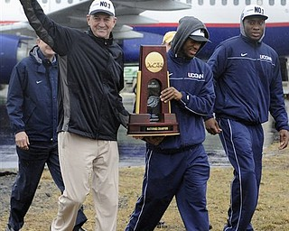 Connecticut head coach Jim Calhoun, left, walks with seniors Kemba Walker, center, and Donnell Beverly, right, as they arrive for a rally at Bradley International Airport in Windsor Locks, Conn., Tuesday, April 5, 2011.  Connecticut beat Butler for the National championship in the NCAA Mens Final Four basketball tournament on Monday, April 4.