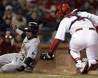 Pittsburgh Pirates' Jose Tabata, left, is tagged out at home by St. Louis Cardinals catcher Yadier Molina during the eighth inning of a baseball game Monday, April 4, 2011, in St. Louis.