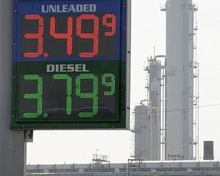 In this March 30, 2011 file photo, a Houston gas station displays its prices with a refinery stack in the background. Quick: What do these things have in common? Libyan leader Moammar Gadhafi. The Japanese earthquake and tsunami. Wall Street volatility. A cranky, even angry American populace. Answer: They all have something to do with gasoline. No matter what happens in the world today, just about everything seems to point back to fuel and the tricky politics that emerge when prices spike.