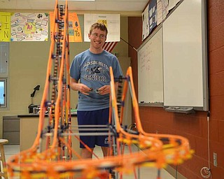 Jackson Milton High School students are competing in a nationwide competition to build a unique roller coaster using only K'NEX pieces. Senior Bobby Collins holds the car his team designed to ride its roller coaster, which features two hills and a downward spiral.