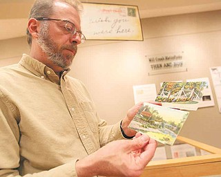 "Keith Kaiser, horticulture director for Mill Creek MetroParks, discusses two of his favorite postcards featured in the ""Wish You Were Here"" display. The display showcases about 150 vintage postcards of the park that Kaiser has collected through sales and auctions over the past 20 years."