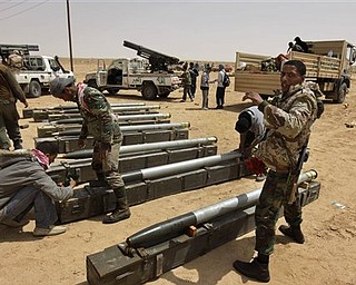Libyan rebel fighters prepare rockets for use at a position west of Ajdabiya, Libya, Wednesday, April 6, 2011. NATO rejected criticism from Libyan rebels over the pace of its military campaign in Libya, saying Wednesday that its airstrikes against Moammar Gadhafi's forces are increasing every day.