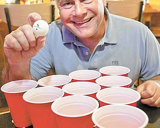 Chuck Zarbaugh shows off his beer-pong gear at Buffalo Wild Wings restaurant in Boardman. Zarbaugh created the Mahoning Valley Beer Pong League, which he said will begin in May. Zarbaugh's version of the game substitutes water for beer to attract young people to the sport.