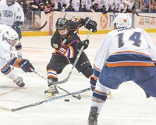 The Youngstown Phantoms' Cody Strang (19) looks for an opening between the Indiana Ice's Nick Mattson (27) and Jarrod Rabey (14) during their USHL game Friday at the Covelli Centre. The Phantoms' 8-6 win and a loss by Waterloo keeps Youngstown in the hunt for a playoff berth.
