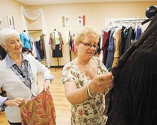 Rhonda Daily (right) looks at clothes in the boutique section while talking to volunteer Ida Lake at Hillcrest Thrift Shop in Kansas City, Missouri. Thrift stores are now starting to resemble regular retail locations. (Garvey Scott/Kansas City Star/MCT)