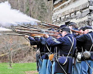 Members of the Western Pennsylvania Civil War Reenactors Society fire their rifles during a spring drill Saturday afternoon at the Raisch Log Cabin in Sharpsville Community Park in Sharpsville, Pa.