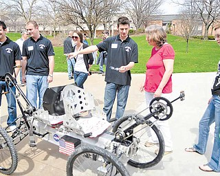Youngstown State University senior mechanical-engineering student Kevin Miller speaks to Susan Halley of Pittsburgh about the moon buggy he and fellow students built. The lunar vehicle was one of many projects the YSU College of Science, Technology, Engineering and Mathematics displayed as attractions at Sunday's annual STEM showcase at Moser Hall.